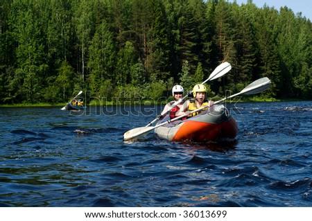 Kayakers sporting a kayak cuts through water - stock photo