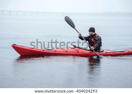 kayaking in cold and rainy weather near the shore - stock photo