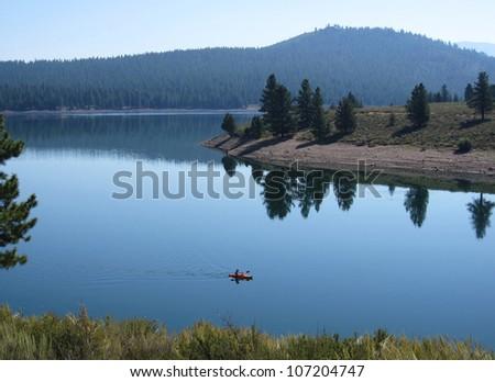 Kayaking in the glassy calm water of the Prosser reservoir near Lake Tahoe - stock photo