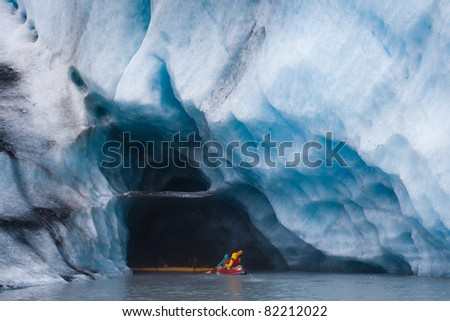 Kayaking into blue ice cave in glacier iceberg, Alaska - stock photo