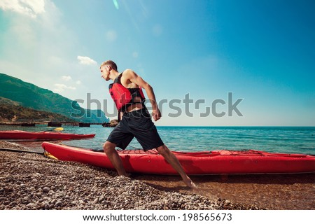 Kayaking. Man pulls a kayak to shore beach. Leisure activities on the sea.  - stock photo