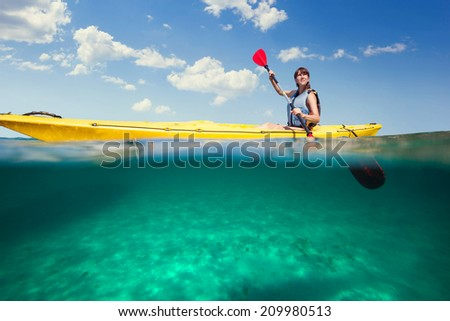 Kayaking. Woman traveling by kayak floating in the sea. - stock photo