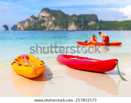 Kayaks on a tropical beach, shallow depth of field. Active holidays background. - stock photo