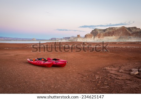 Kayaks Sit on the Receding Shoreline of Lake Powell (Glen Canyon National Recreation Area) - stock photo