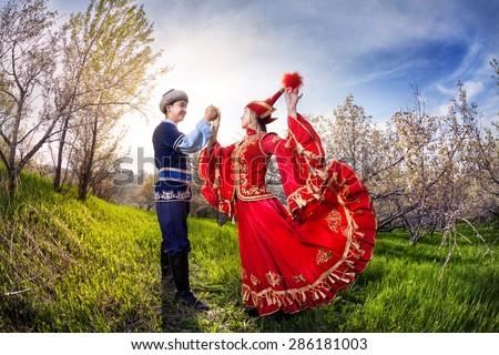 Kazakh woman dancing in red dress with man in Spring apple garden in Almaty, Kazakhstan, Central Asia - stock photo