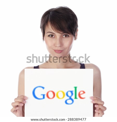 KAZAN, RUSSIA - MAY 8, 2015: Girl holds Google logo printed on paper. Warning: logo printed in especially big pixels. Google is corporation specializing in Internet-related services and products. - stock photo