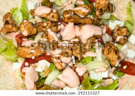 Kebab gyros salad with grilled chicken and vegetables topped with sauce, macro close-up, food background - stock photo