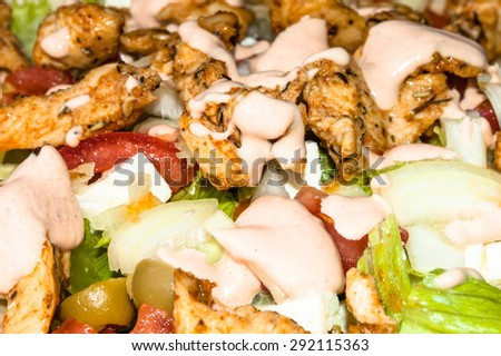Kebab gyros salad with grilled meat and vegetables topped with sauce, macro close-up, food background - stock photo