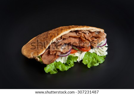 Kebab in pita bread isolated on black background - stock photo