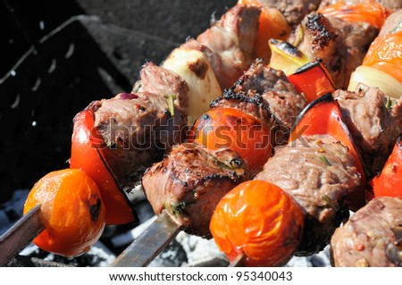 Kebabs, threaded on a skewer and grill. - stock photo