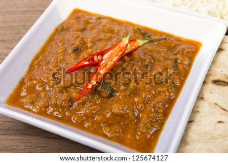 Keema Madras - Minced lamb curry garnished with chilies and served with rice and chapatis. - stock photo
