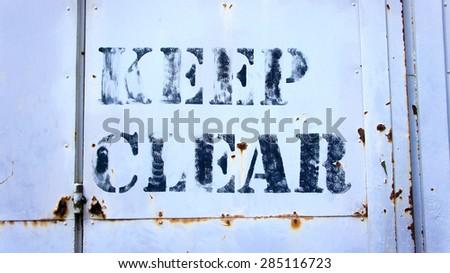 Keep Clear sigh on rusty metal door - stock photo