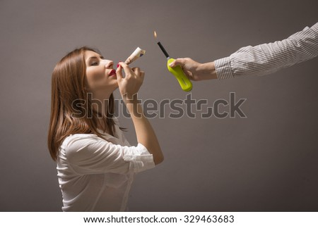 Keep health and save money - quit smoking! Burning away money. Spending money on addictions. Woman holding a cigarette made out of paper money. - stock photo
