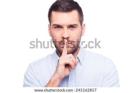Keep my secret!  Serious young man in shirt holding finger on lips and looking at camera while standing against white background - stock photo
