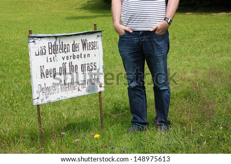 Keep off the grass / Young man ignores Information sign for park visitors - stock photo