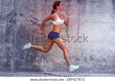 Keep on running.  Full length side view of beautiful young woman in sports clothing running with a concrete wall in the background - stock photo