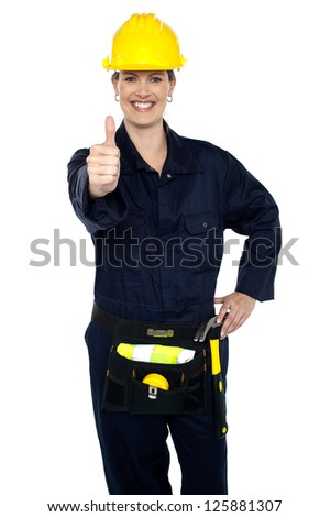 Keep up the good work. Confident lady worker showing thumbs up to you. - stock photo