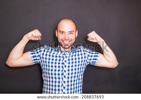 Keeping fit man shows his muscles , isolated on black background - stock photo