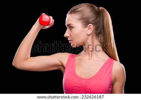 Keeping her body fit. Sporty young woman exercising with dumbbell while standing against black background - stock photo