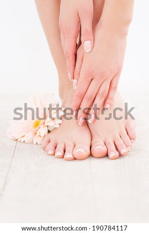 Keeping her feet clean and smooth. Close-up of woman touching her feet while standing on hardwood floor - stock photo