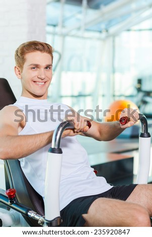 Keeping his body fit. Handsome young man working out in gym and smiling - stock photo