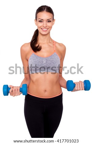 Keeping my body toned. Shot of a beautiful and sporty young woman lifting up weights against white isolated background. - stock photo