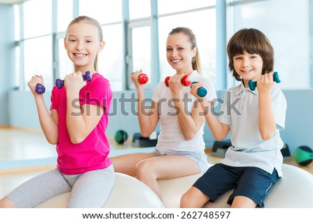 Keeping our bodies fit. Cheerful mother and two children exercising with dumbbells in health club while sitting on the fitness balls together - stock photo