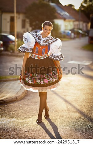 Keeping tradition alive: young woman in a richly decorated ceremonial folk dress/regional costume (Kyjov folk costume, Southern Moravia, Czech Republic) - stock photo