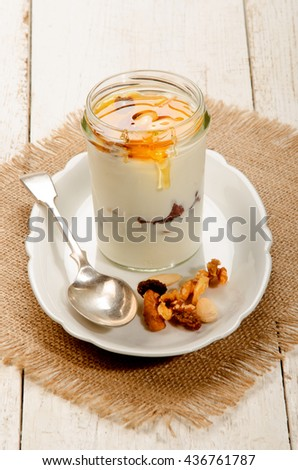 kefir in a glass with sweet honey, nuts and fruit and spoon on oval plate - stock photo