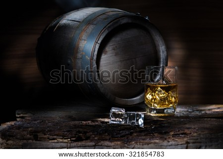 Keg and a glass of whiskey on a wooden table - stock photo