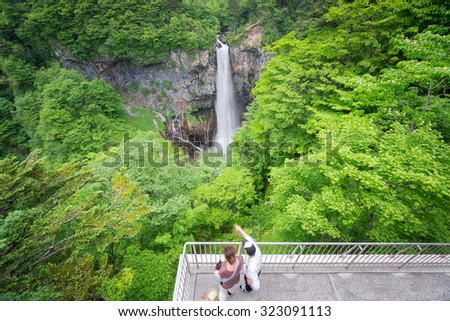 Kegon Falls in Nikko with blurred tourists, One of the top 3 waterfalls in Japan, wide angle view, silk water - stock photo