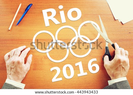 KEMEROVO, RUSSIA - JUNE, 25, 2016. Man cuts olympic symbols of paper. Abstract conceptual image about Olympics in Brazil - stock photo