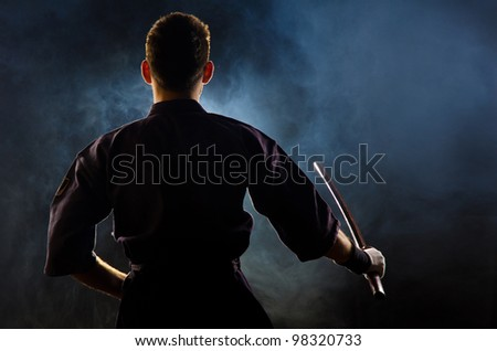 kendo fighter with bokken. dark background with smoke and dynamic light. - stock photo
