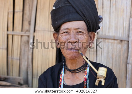 KENGTUNG, MYANMAR - JANUARY 20, 2016: A portrait of an Akhu hill tribe woman smoking her pipe in her village in Kengtung. The Akhu are an indigenous hill tribe living in Eastern Myanmar. - stock photo
