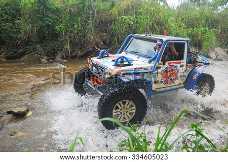 Keningau Sabah Malaysia - Nov 1, 2015:Adventure car enthusiast wading a rocky river  using modified four wheel car in the jungle of Sabah Borneo.Jungle of Borneo is famous for 4x4 adventure tourism. - stock photo