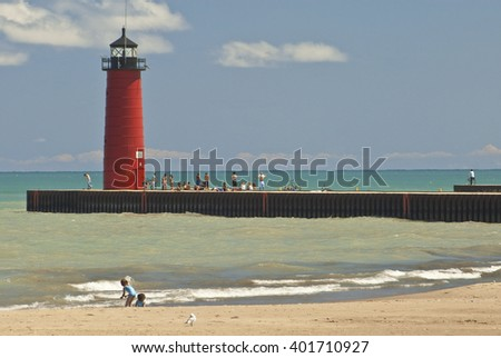 Kenosha Wisconsin's Pierhead Light attracts a crowd of young beach goers in summer - stock photo