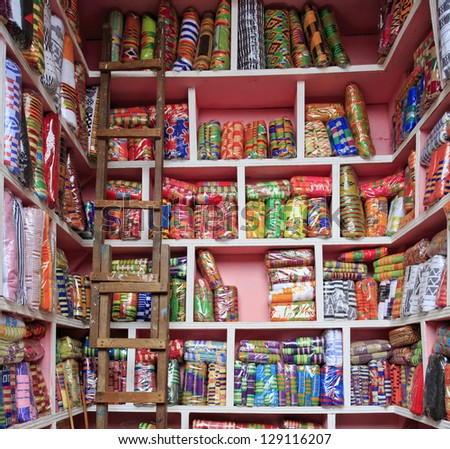 Kente cloth for sale at the market with a ladder - stock photo