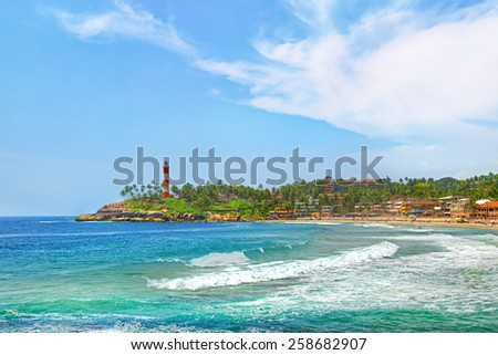 Kerala province beach in India with a vivid lighthouse in the ocean - stock photo