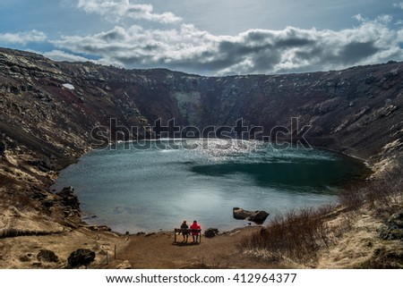 Kerid, volcanic crater lake of Iceland, is located in Golden Circle route. A couple enjoy seeing the scenery - stock photo