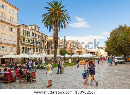 KERKYRA, GREECE - SEPTEMBER 16: View to the Kapodistriou street with cafe tables and tourists shown on 16 September 2013 in Kerkyra, Greece.  - stock photo