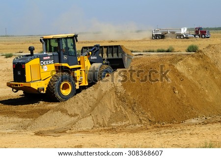 KERN COUNTY, CA - AUG 20, 2015: A front end loader scoops up excess dirt on a construction project as a bottom dump truck approaches to receive the material. - stock photo