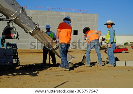 KERN COUNTY, CA - AUGUST 11, 2015 : A transit mix truck delivers concrete down a chute while workers place the wet material in a ditch to serve as a footing for a block wall. - stock photo