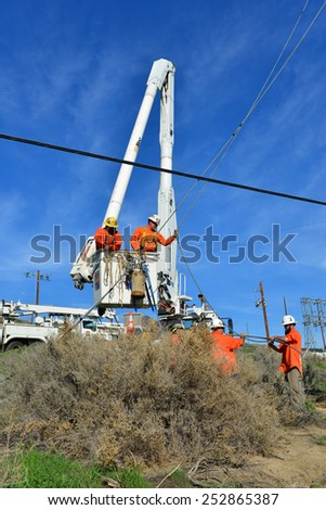 KERN COUNTY, CA - FEBRUARY 14, 2015: The crew of a contractor to PG&E uses a hydro crane with a basket to set a new wood pole and stabilize it with guy wires in difficult terrain. - stock photo