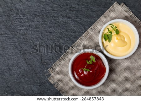 ketchup and mayonnaise - two kinds of sauces on black background top view - stock photo