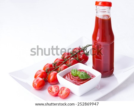 ketchup, catsup in a glass bottle and a white bowl with cherry panicles tomatoes isolated on white background, copy space - stock photo