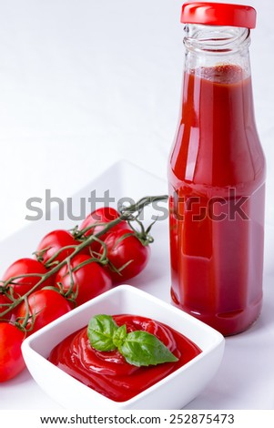ketchup, catsup in a glass bottle and a white bowl with cherry panicles tomatoes isolated on white background, vertical closeup - stock photo