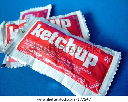 Ketchup packets on blue background, close up - stock photo
