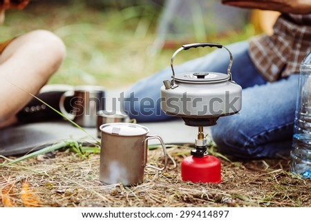 kettle boiling on a gas stove in the forest camping - stock photo