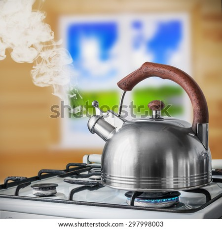 kettle boiling on the gas stove in the kitchen. Focus on a spout - stock photo