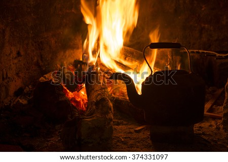 Kettle in fireplace, fire and wood burning. Cozy winter holiday cabin scene. - stock photo